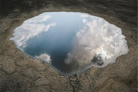 flat - Rain drops falling onto a large puddle. A reflection of sky and clouds. Stock Photo - Rights-Managed, Code: 878-07442484