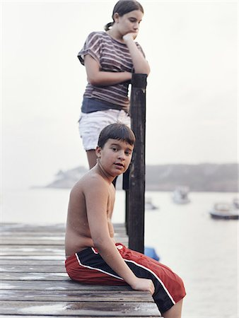 Two young people, teenagers, boy and girl, on a dock overlooking moored boats on the coastline. Stock Photo - Rights-Managed, Code: 878-07442509