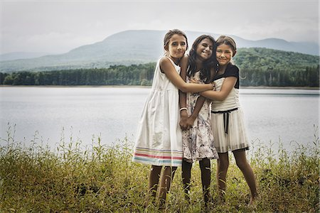 elementary age - Three young girls standing by the side of a lake, hugging each other. Stock Photo - Rights-Managed, Code: 878-07442514