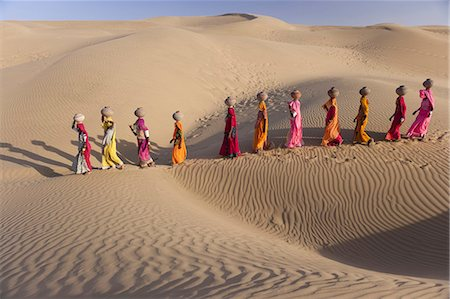 desert people dress photos - Women bear the responsibility of fetching water from the sparse wells within Rajasthan's vast Thar Desert. Trekking up the side of a sand dune, women expertly balance large clay water vessels atop their heads. Rajasthan, India Stock Photo - Rights-Managed, Code: 878-07442705