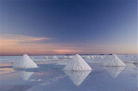 salt - The salt pans of Salar de Uyuni, with shallow water and mineral deposits. White salt granules raked into heaps. Stock Photo - Rights-Managed, Code: 878-07442784