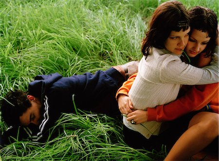 sad lovers break up - Women Hugging, Man Lying in Grass Stock Photo - Rights-Managed, Code: 873-06441139