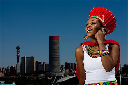 Traditionally dressed African woman talks on cellphone with cityscape in background Stock Photo - Rights-Managed, Code: 873-07156697