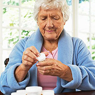 Senior Woman Looking at Pill Bottle Label