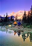 Couple Riding Bikes near Lake Bow Lake, Banff National Park Alberta, Canada