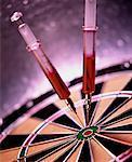 Close-Up of Syringes on Dartboard