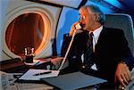 Ältere Businessman im Flugzeug telefonieren