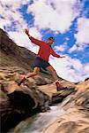 Homme sautant à travers des cours d'eau le Parc National Yoho en Colombie-Britannique, Canada