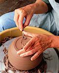 Gros plan des mains du potier féminin sur terre battue à l'aide d'outil