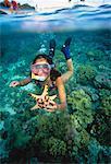 Girl Snorkelling Underwater Holding Starfish, Philippines