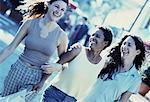 Three Women Walking Arm in Arm on Street, Smiling