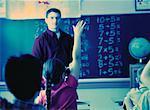 Enseignant de sexe masculin regarder la jeune fille à main levée dans la salle de classe