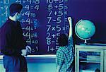 Lehrer beobachten Boy schreiben an die Tafel im Klassenzimmer