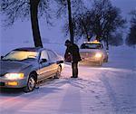 Man Refuelling Stalled Car in Winter, Ottawa, Ontario, Canada