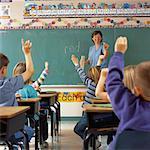 Enseignante à l'ardoise et les étudiants avec les mains levées