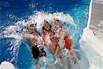 Three Children Jumping Backwards In Swimming Pool