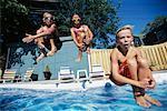 Trois enfants sautant dans une piscine