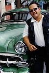 Portrait of Man Wearing Sunglasses, Leaning on Antique Car, Havana, Cuba