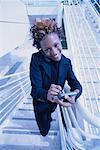 Porträt der Geschäftsfrau, die mit Handy und elektronische Organizer auf Treppen
