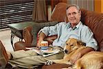 Man Sitting on Sofa with Dog