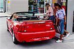 Teenage Girls Putting Gas in Car