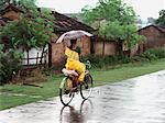 Woman Riding Bicycle in Rain