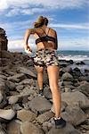 Femme en cours d'exécution sur les rochers