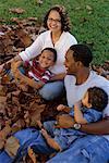 Familie in Blätter sitzen