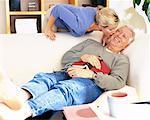 Man Resting on Sofa and Woman Kissing Him on Cheek