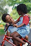 Mother Helping Daughter Ride Bike