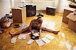 Woman Sitting on Floor, Doing Finances