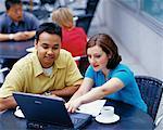 Homme et femme avec ordinateur portable dans le Cafe