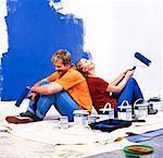 Seitenansicht eines Paares sitzen Rücken an Rücken mit Walze Pinsel Farbe in der hand