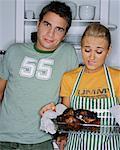 Couple dans la cuisine, femme tenant dîner brûlé