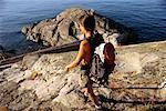 Woman Hiking on Rocky Shoreline