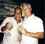 portrait of two elderly men holding their drinks