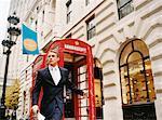 Businessman Leaving Phone Booth, London, England