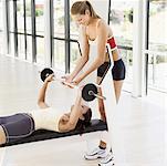 Seitenansicht eines weiblichen Instructor hilft einer jungen Frau, die mit Gewichten trainieren