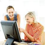 Porträt von zwei jungen Frauen vor dem Computer vor Lachen