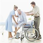 female nurse and a mid adult man helping a senior man into a wheelchair