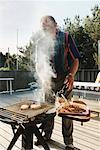 Man Barbecuing in Backyard