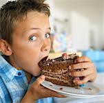 Nahaufnahme eines jungen (8-10), ein Stück Schokolade Kuchen essen
