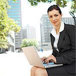 Porträt einer geschäftsfrau saß unter einem Baum auf einem Laptop arbeiten