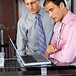Seitenprofil von zwei Geschäftsleuten Anzeigen von einen Laptop-Bildschirm bei der Arbeit