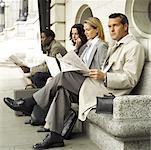 eine Gruppe von Menschen auf einer steinernen Bank sitzen und warten