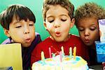 Jungen Ausblasen der Kerzen auf der Geburtstagstorte