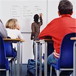 Étudiant par écrit sur le tableau blanc dans la salle de classe