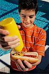 Boy Putting Mustard On Hot Dog