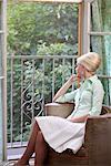 Woman Sitting by Open Window