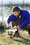 Homme de cuisson sur la cuisinière de Camp Camping voyage